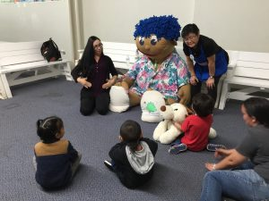 Members of the CSC Ohana Time group interact with Stuffee at Hawaii Children's Discovery Center.